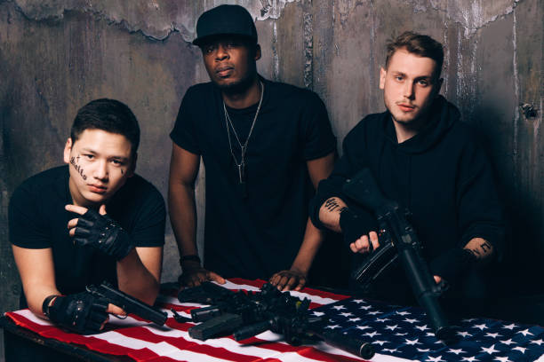 American gangs with weapons American gangs with weapons. Interracial young people with tattoos hold guns and rifles in their hands. Outlaw, ghetto, murderer, armed attack concept american flag tattoos for men stock pictures, royalty-free photos & images