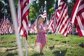4 year old American girl in a big field of American flags.