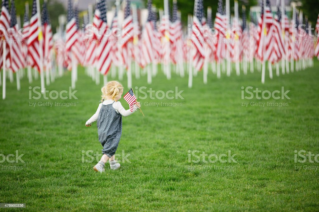 American girl walking in a field of flags stock photo