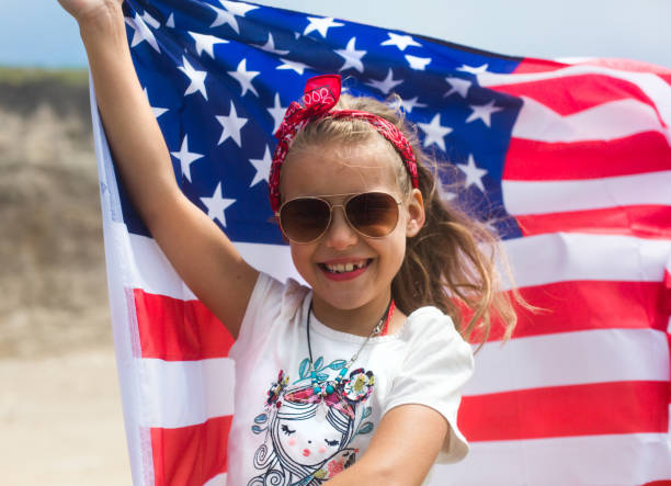 American girl with American flag. Little smiling patriotic girl holding an american flag waving in the wind on the ocean beach. National 4 july. Memorial day. Independence day. Flag day American girl with American flag. Little smiling patriotic girl holding an american flag waving in the wind on the ocean beach. National 4 july. Memorial day. Independence day. Flag day Anglo American stock pictures, royalty-free photos & images