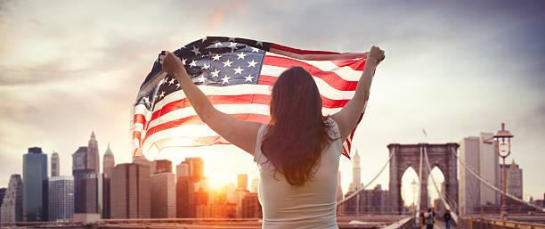 American girl with us flag on Brooklyn bridge in NYC stock photo