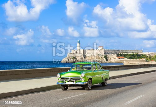 American green 1952 vintage car on the promenade Malecon and in the background the Castillo de los Tres Reyes del Morro in Havana City Cuba - Serie Cuba Reportage