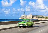 American green 1952 vintage car on the promenade Malecon and in the background the Castillo de los Tres Reyes del Morro in Havana City Cuba - Serie Cuba Reportage