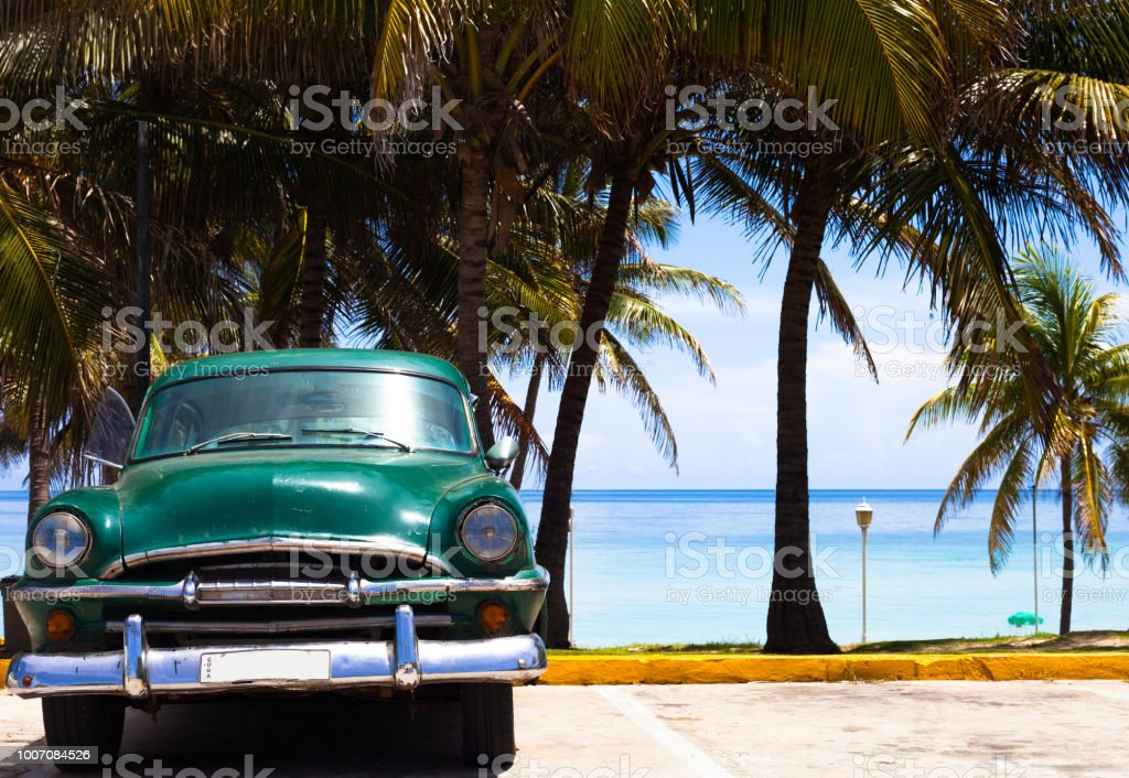 American green classic car in the front view on the beach in Varadero...