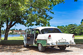 American green white classic car with open door parked under a tree on the beach in Varadero Cuba -Serie Cuba Reportage