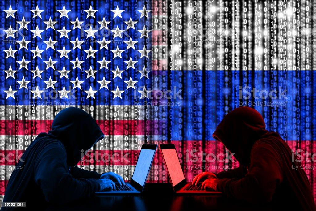 American hacker sitting opposite of a russian hacker cyberwar concept stock photo