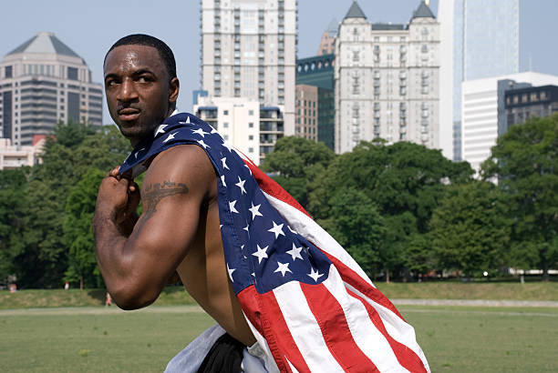American Hero - Muscular Man This muscular man wraps the flag around his neck like it was his cape....about to fly off to fight crime. american flag tattoos for men stock pictures, royalty-free photos & images