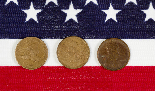 Closeup view of United States One Cent Pieces, original start dates, placed on American Flag
