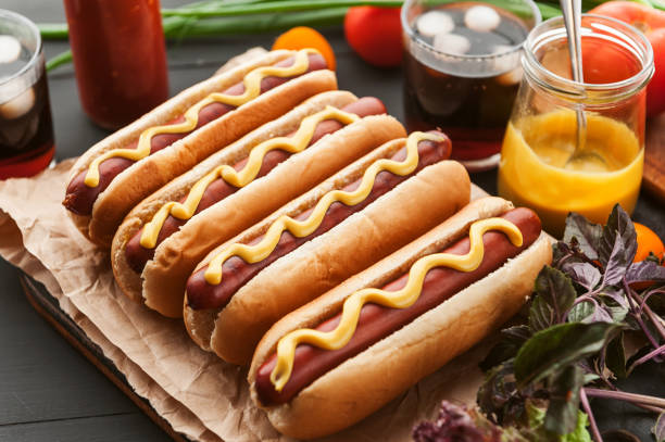 American hot dog with ingredients on a dark wooden background stock photo