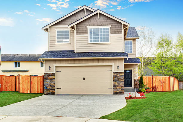 American house exterior with beige trim, garage with concrete driveway American house exterior with beige trim, garage with concrete driveway and brown fence with well kept lawn around stone house stock pictures, royalty-free photos & images