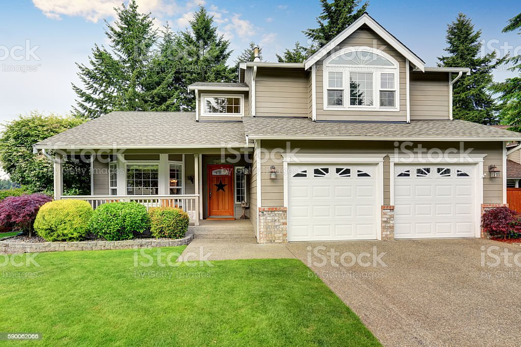 American house exterior with double garage and well kept lawn. – Foto