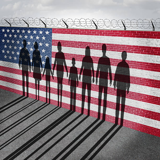 American Immigration American immigration and United States refugee crisis concept as people on a border wall with a US flag as a social issue about refugees or illegal immigrants with the cast shadow of a group of migrating women men and children. international border barrier stock pictures, royalty-free photos & images
