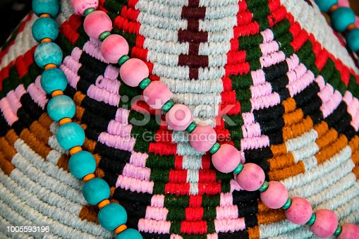 istock American Indian decor background - pink and turquoise beads draped on a colorful textile woven design closeup and shallow focus 1005593196