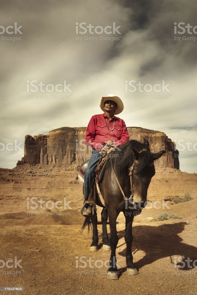 American Indian Navajo Cowboy Riding Horse in Southwest USA Vertical stock photo
