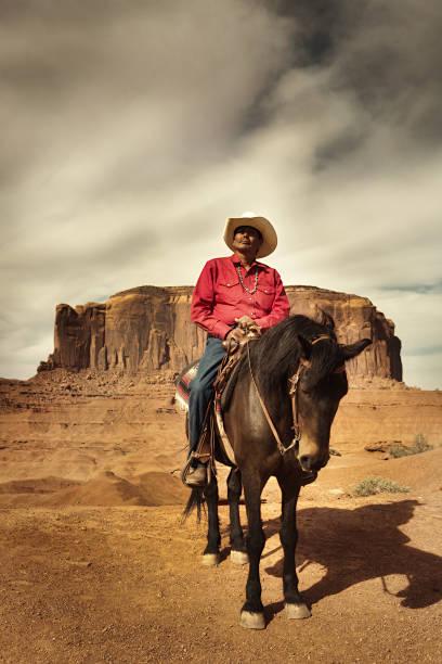 american indian navajo cowboy auf pferd im südwesten der usa vertikal - navajo stil stock-fotos und bilder