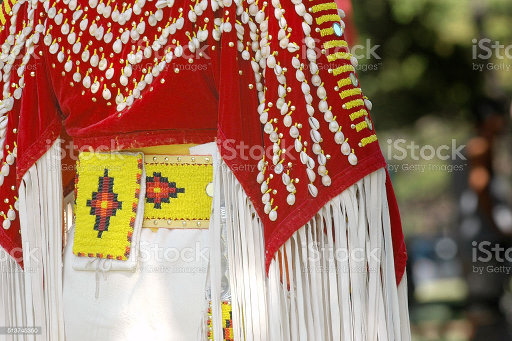 American Indian traditional costume in red and white with shells stock photo