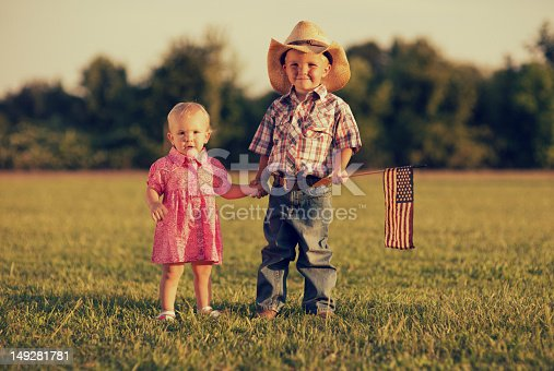Two young siblings pose for a portrait in the summer sun. Happy 4th of July.