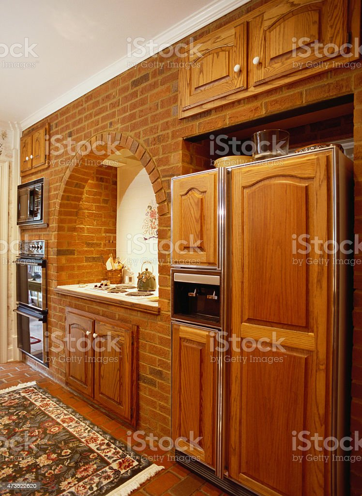 American kitchen with brick wall and oak doors and cabinets. stock photo