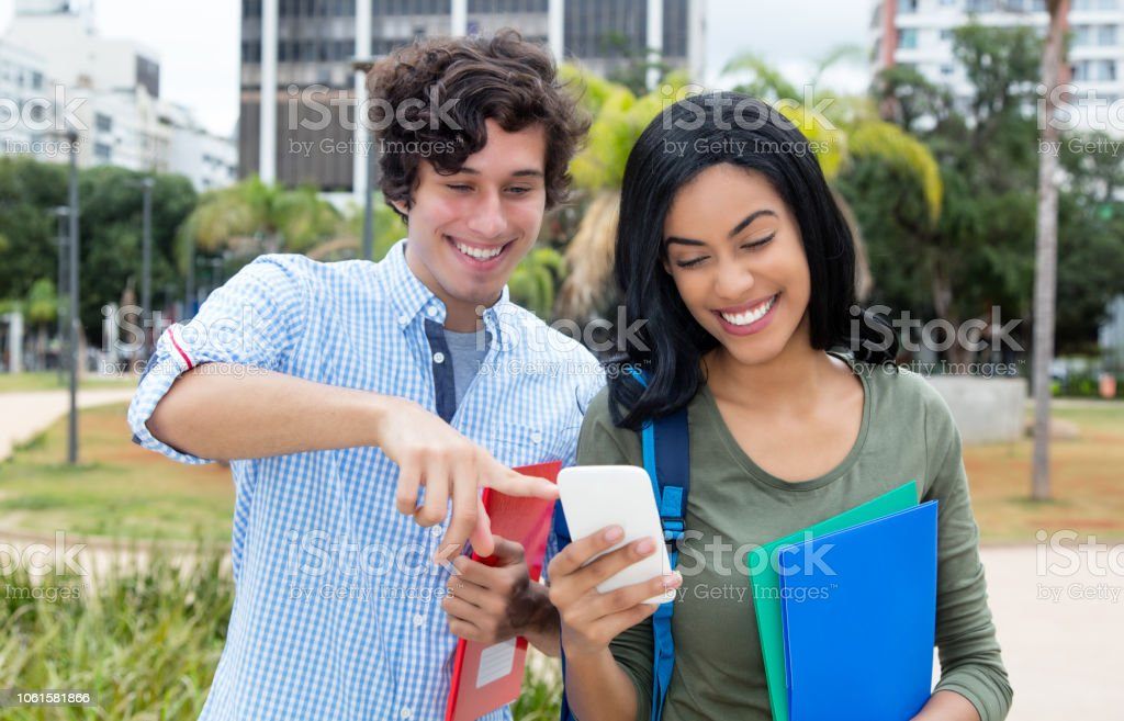 American male student and indian girl looking at mobile phone stock photo
