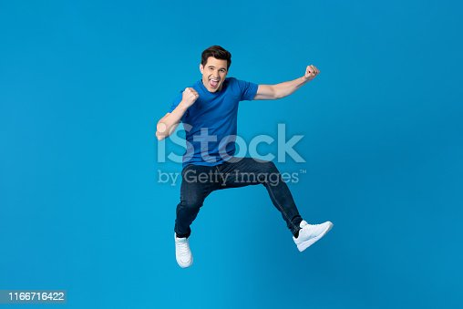 Smiling handsome American man joyfully jumping and raising his fists isolated on blue studio background  fro success and freedom concepts