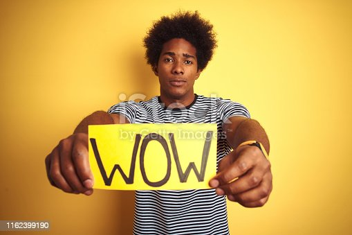 istock American man with afro hair holding wow banner standing over isolated yellow background with a confident expression on smart face thinking serious 1162399190