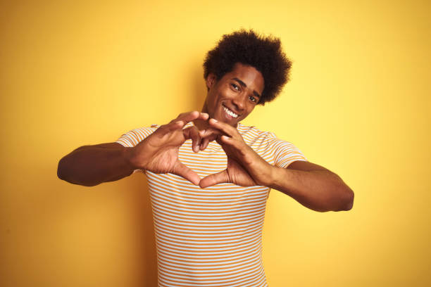 American man with afro hair wearing striped t-shirt standing over isolated yellow background smiling in love doing heart symbol shape with hands. Romantic concept. stock photo