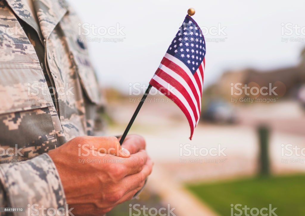 American military soldier with flag. Patriotic theme stock photo
