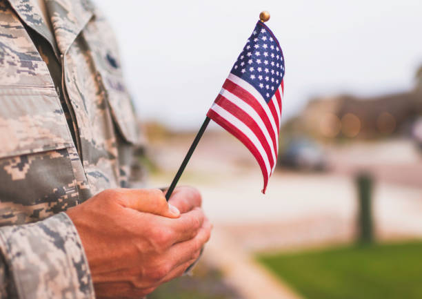 american military soldier with flag. patriotic theme - veterans day стоковые фото и изображения