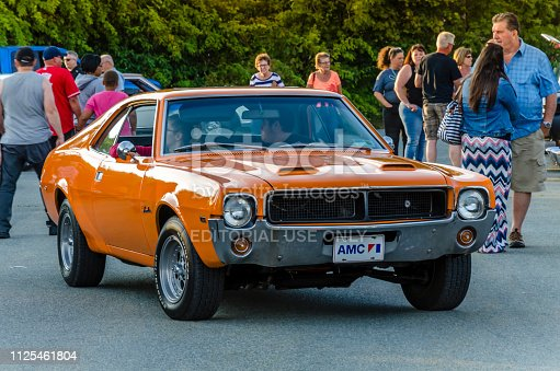 Dartmouth, Nova Scotia, Canada -  August 3, 2017: Owner attempts to avoid the crowd of people as he backs his 1969 AMC Javelin into a parking spot at the summer weekly A&W Cruise-in, Woodside Ferry parking lot. On a beautiful summer evening people walk among the many vintage cars on display by their owners.