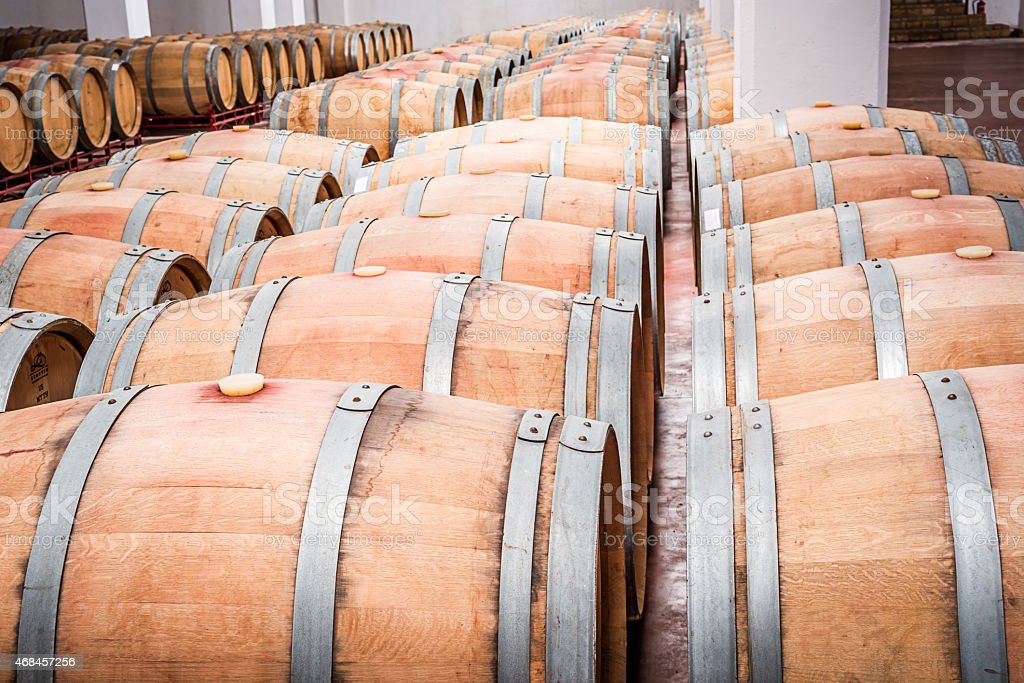 American oak barrels with red wine. Traditional wine cellar stock photo