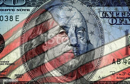 Conceptual finance image of American one hundred dollar bill and American flag