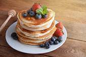 American pancakes with strawberry and blueberry jam, delicious dessert for breakfast, rustic style, wooden background.