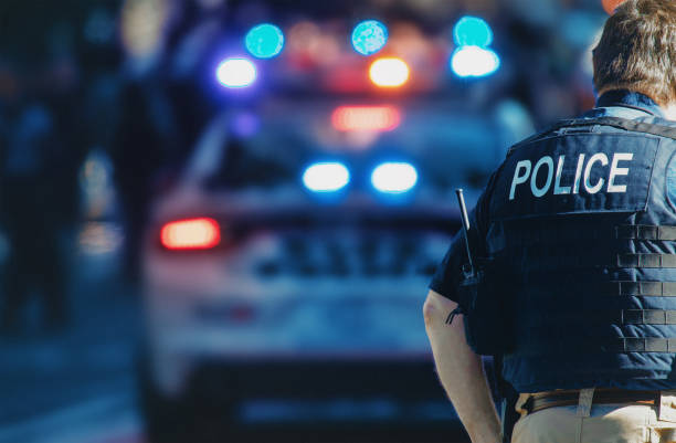 amerykański policjant i samochód policyjny w tle - policja zdjęcia i obrazy z banku zdjęć