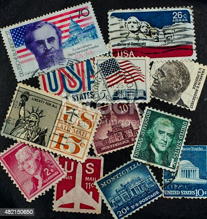 Multiple american postage stamps and one german postage stamp.