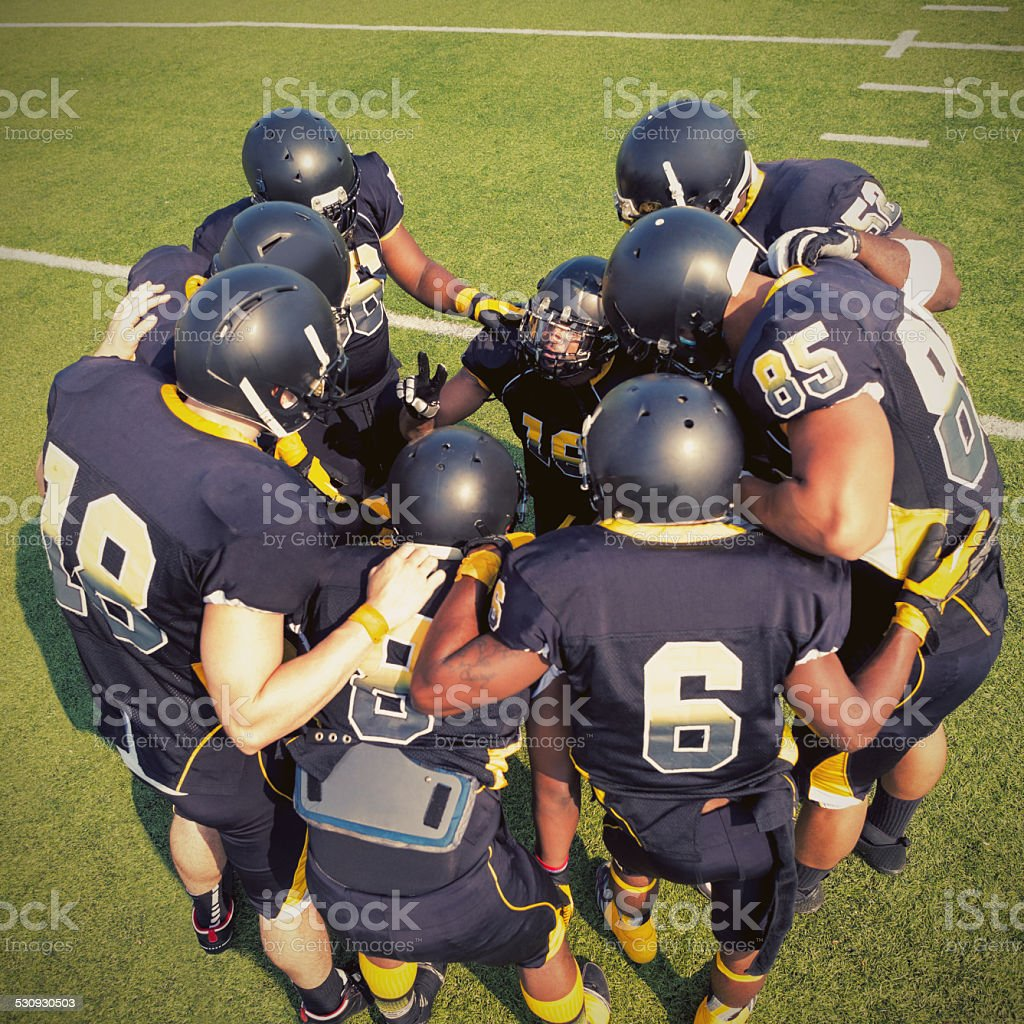 American professional football players huddled together on field stock photo
