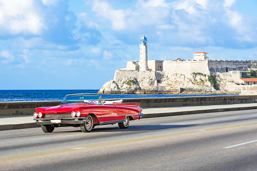 American red 1959 convertible vintage car on the promenade Malecon and in the background the Castillo de los Tres Reyes del Morro in Havana City Cuba - Serie Cuba Reportage