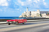 American red 1959 convertible vintage car on the promenade Malecon and in the background the Castillo de los Tres Reyes del Morro in Havana City Cuba - Serie Cuba Reportage