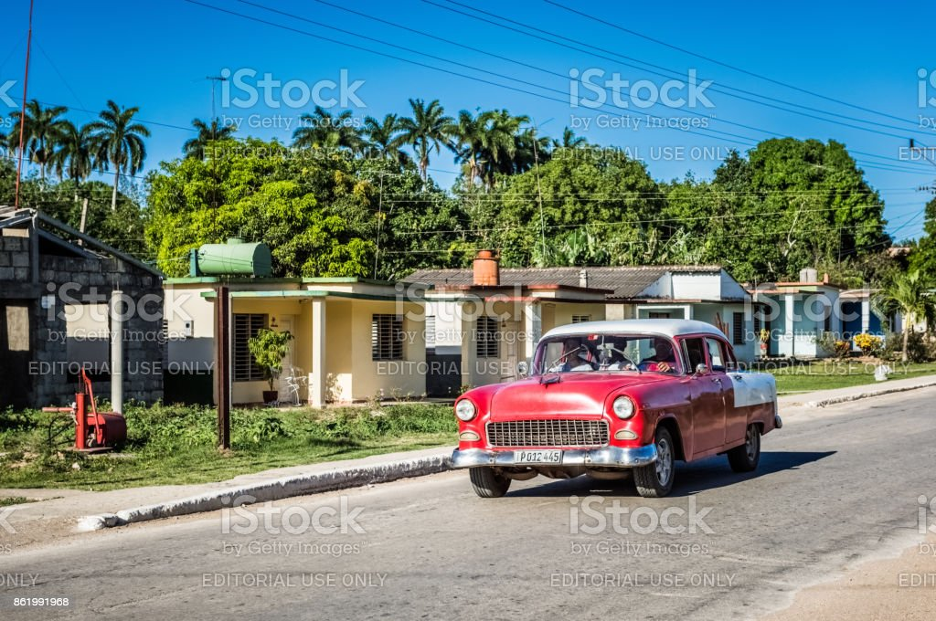 American red Chevrolet with white roof classic car drives on the main street in the suburb from Havana Cuba - Serie Cuba Reportage stock photo