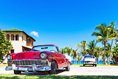 American red convertible and a blue white classic car parked on the beach in Varadero Cuba - Serie Cuba Reportage