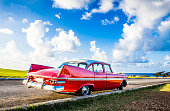 American red vintage car with white roof parked on the castle el Morro in Havana Cuba before the caribbean ocean - Serie Cuba Reportage