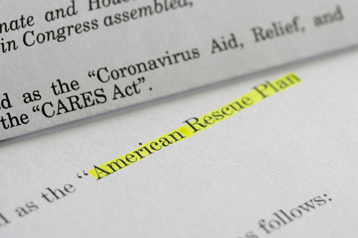Closeup of the documents of both the Cares Act (Coronavirus Aid, Relief, and Economic Security Act) and the American Rescue Plan Act (ARPA) of 2021. A comparison between two acts.