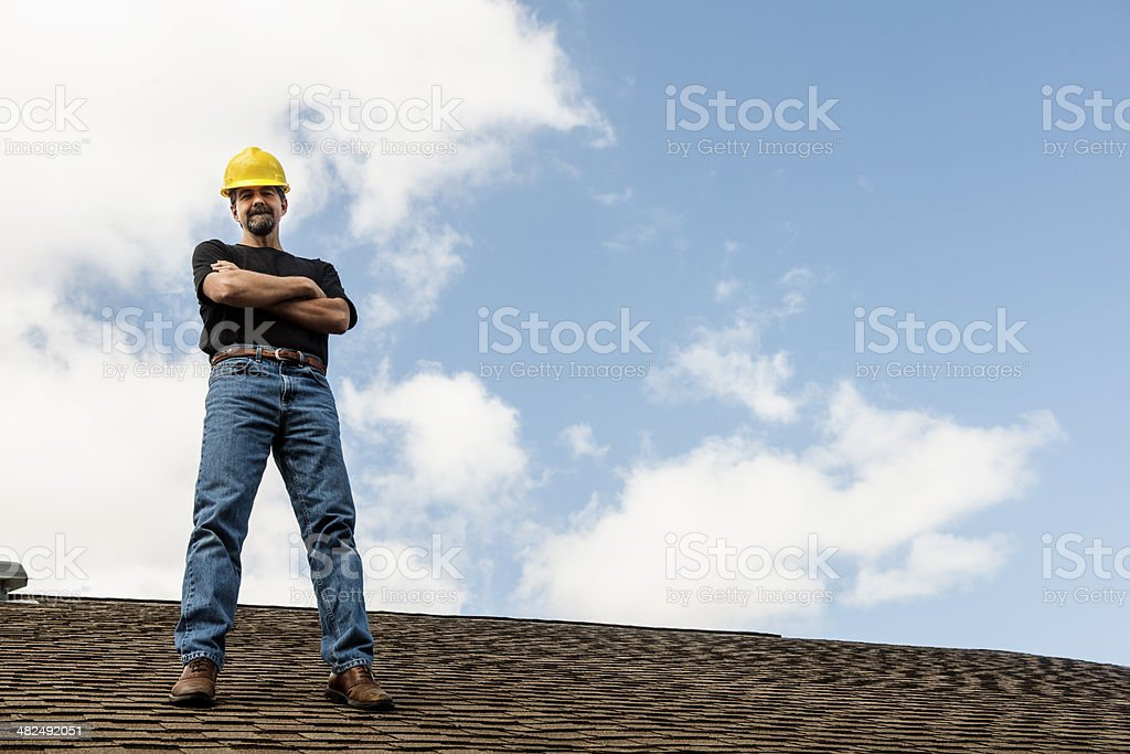 American Roofing Contractor Standing on Home Roof stock photo