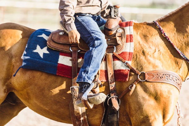 American Saddle Blanket Rider Young boy horse rider with an american flag saddle blanket at a rodeo warm up riding in an arena appaloosa stock pictures, royalty-free photos & images