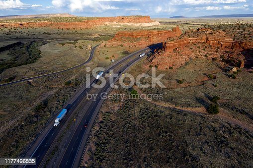 Aerial view of semi trucks on Interstate 40 near a large rock formation, New Mexico, USA.