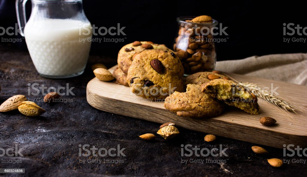 American shortbread cookies with chocolate drops and a jug of milk and almonds. Dark grunge background. Mystical light stock photo