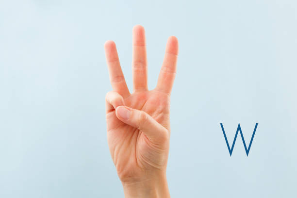 American sign language W. American sign language. Female hand showing letter W isolated on blue background. letter w stock pictures, royalty-free photos & images