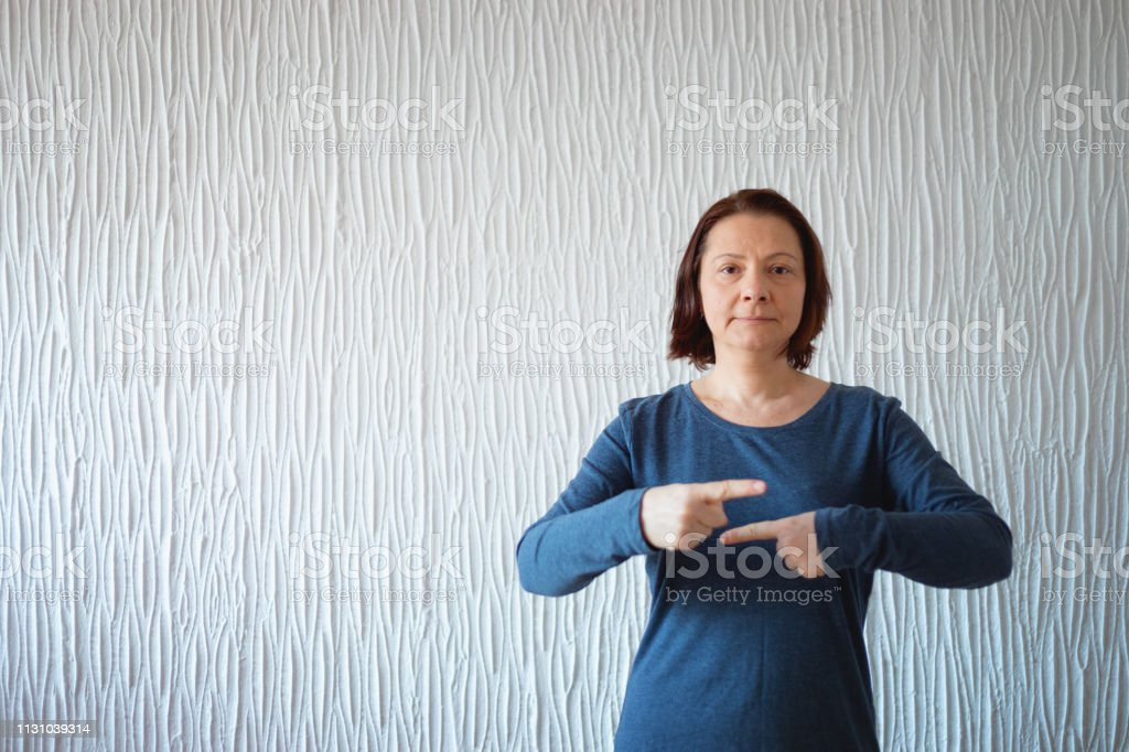 Mid adult woman making gesture, explaining term sign, using American...