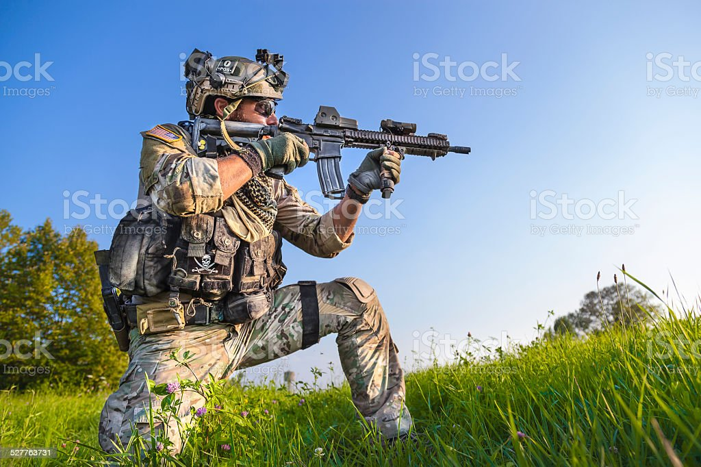 American Soldier aiming his rifle on blue sky background stock photo
