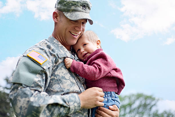 american soldier and son in a park - armed forces stock photos and pictures