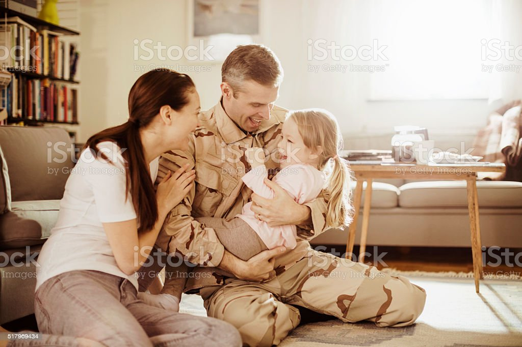 American soldier finally at home with his family stock photo